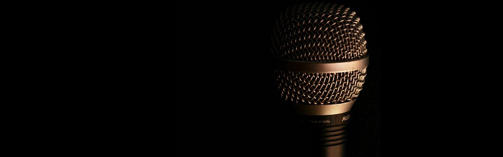 Guld mikrofon mot svart backgrund